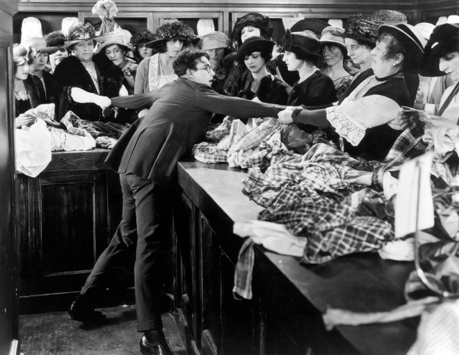1923: American actor and comedian Harold Lloyd (1893 - 1971) is pulled in different directions by women in fabric store in a still from the film, 'Safety Last' directed by Fred C Newmeyer and Sam Taylor.